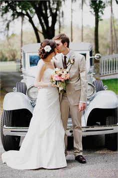 beautiful shot of the bride and groom with vintage getaway car
