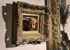 A carved German angel on aged mirror and framed