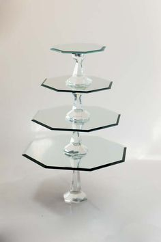 ^How to Make Mirrored Cake Stands withInterchangeable Variable Height Bases:    Mirrors in graduated sizes. I used 12, 10, 8, and 6 inch diameter sizes.  Candlesticks (in two different heights)  E6000 glue  super strong magnets  Fimo dough, in white or silver