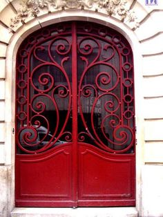 red wrought iron scroll doors, house, concrete surround