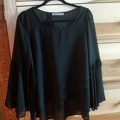 Black chiffon top Bell sleeves with Embroidered detail.  Never worn.  Layered detail in the front.  Front of fully lined.  Could fit large also. entro Tops Tunics