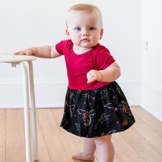 Watch out! Fierce, beautiful dragons circle this print, breathing fire of scarlet and sparkling gold on a scarlet snapsuit. It's sure to be a favorite for your Little Dragon Tamer.  Sizes 3 months, 6 months, 9 months, 12 months, 18 months.