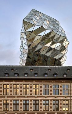 Zaha Hadid Architects has topped off its crystalline addition to an old fire…