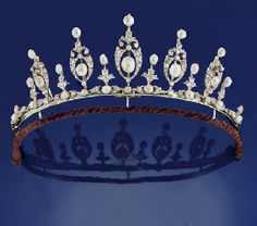 A LATE VICTORIAN DIAMOND AND PEARL TIARA/NECKLACE   Composed of a series of graduated openwork cartouche shaped panels each centrally set with a pearl, within a border of old-cut diamonds, with stylised diamond foliate intersections, pearl terminals and flexible line connections, mounted in silver and gold, circa 1890, later rope-link backchain and fitted case by Collingwood Ltd.