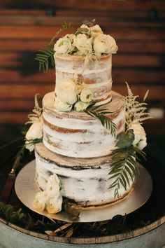 Naked three tier wedding cake with white flowers and rustic greenery | Sarah Godenzi Photography