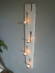 Bent spoons & tea lights on white washed board <3
