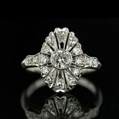 A truly delightful Art Deco ring in platinum. This gem-of-a-ring has a pleasing marquise shape and is centered with a carat European-cut diamond. Small accent diamonds are set in slight petal shapes surrounding the center diamond amidst delicate pierc Bijoux Art Deco, Art Deco Jewelry, Fine Jewelry, Jewelry Design, Jewellery, Women Jewelry, Antique Rings, Vintage Rings, Antique Jewelry
