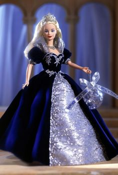 "1999 - Millennium Princess™ Barbie® Doll | Barbie Collector Millennium Princess™ Barbie® doll is dressed in a magnificent royal blue velvety gown with shimmering organza and silvery glitter lace cascading down the front. A lovely tiara, sparkling necklace, and a ""crystal"" ball keepsake ornament make her a beautiful way to welcome the year 2000!"