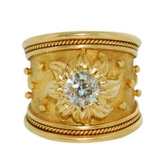 Gorgeous 18K yellow gold tapered templar ring, featuring 0.85 carat round brilliant diamond, with flower designed surround. The ring is decorated with gold bead detail and is finished with a wire twist wire edge