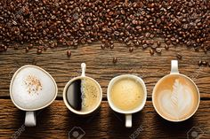 Variety Of Cups Of Coffee And Coffee Beans On Old Wooden Table ...