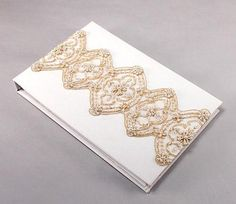 Luxe Wedding Guest Book covered in satin available in white or ivory.  The design features an elaborate gold beaded design that gives the allure of vintage inspired lace. This wedding guest book is available in ivory or white, but the beading color remains the same for both styles.