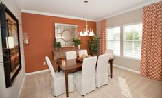 This dining room from @Lennar Jacksonville in Bainebridge Estates has the perfect pops of orange with an accent wall and trendy curtains