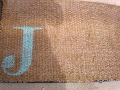 So clever!  Use spray paint and a stencil to make a monogram outdoor mat.