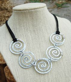 Bold Spiral Link Necklace, Silver, Aluminum Wire, Wire Jewelry. $49, by Karisma by Kara Jewelry (Designs in Aluminum & Copper) via Etsy. Bold spirals using aluminum wire, hammered to work harden and add texture. A soft black deerskin cord (doubled) finishes off the look. A heavy look that is very lightweight.