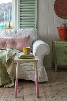 a beautiful painted stool and soft pink cushion on a sofa