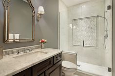 Elegant bathroom boasts dark gray walls framing a Queen Anne style mirror flanked by a nickel wall sconce over an espresso sink vanity with marble counter and porcelain sink accented by a slim marble mosaic backsplash.
