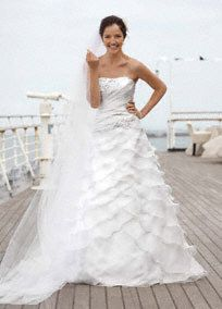 High-fashion meets affordable in this eye-catching organza gown.  Strapless bodice features intricate beaded floral detail for a glamorous touch.  Ruching creates a flattering effect.  Tiered organza skirt is on trend and shapes a stunning A-Line silhouette.  Available in limited stores in Soft White.