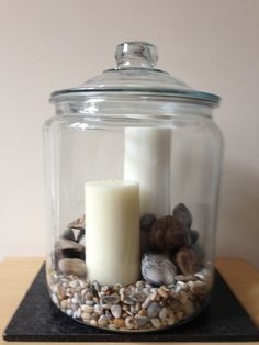 large glass jar with river and sea stones church candles