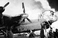 Fire crews attempt to save an Avro Lancaster at Melsbroek, after an attack on the airfield by Luftwaffe bombers.