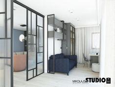 Ciemno niebieska kanapa, przeszklone drzwi, geometryczne szafki, miękkie firanki, widok na salon