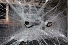 With its long, hollow tubes suspended five feet in the air from surrounding walls and pillars, the packing tape cocoon is like a giant artistic bounce house/jungle gym for adults, who can crawl inside and lounge around, comfortably supported by 117,000 feet and 100 pounds of tape.