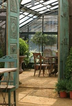 Conservatory by the side of the cottage with the plants and patio furniture