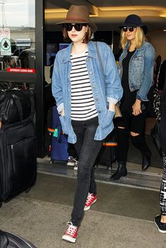 Dakota Johnson in a Rag & Bone Floppy Brim Wool Fedora Hat, striped tee, and red Converse Chuck Taylor All Star Sneakers