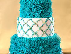 The bride I made this for, is a friend of our family, so she let me create whatever I wanted for her bridal shower.  Her wedding is a peacock theme, so I used those colors as inspiration.  The top and bottom tier I piped teal buttercream ruffles.  The middle tier is covered with fondant, then I stenciled it with a teal quatrefoil pattern.  Then I painted over that with gold highlighter dust mixed with vodka.  I placed a gold hand made gumpaste flower on top, and in the center of the flower…