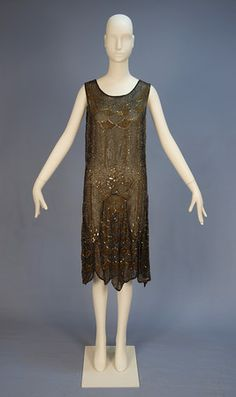 BEADED CHIFFON FLAPPER DRESS. Sleeveless black silk having allover pattern of scallops and geometric vertical bands in gold and crystal beads with iridescent sequins, floral mid-band, scalloped hem with two slits to both front and back, no under dress