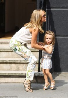 Mummy's got you: Amanda was seen holding onto her daughter¿s hand as they left the shop before leaning down to carry her tot
