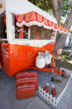 Exterior view of 1960 Orange and White Shasta Trailer and luggage at Vintage…