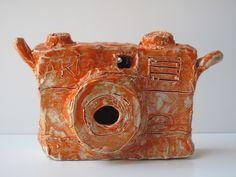 "PBS Arts shares Alan Constable's ceramic camera collection - Orange AKI SLR, 2011. Ceramic, 6 x 10 x 4""."