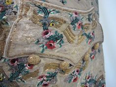 Embroidery detail of waistcoat pocket, 1770-1790, America, silk and chenille embroidery. Gold thread embroidered with florals in colored silk threads, flowers and vines in colorful chenille thread, twelve gold embroidered front buttons, low shaped pocket flaps, knapped linen back, silk facings, linen/cotton fustian linings. Full waistcoat here: http://pinterest.com/pin/278589926921441015/