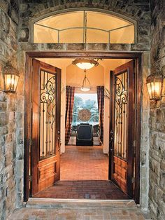 Marked by an exterior central tower and a stone-covered portico, the entrance to Salado View heightens the anticipation of what awaits. As you pass through double 8-foot-tall mahogany doors with decorative ironwork, the brick flooring continues inside. Interior designers David Collum, Mary Collum, and Stephanie Latham mixed bricks in hues of tan, gray, and red to achieve a pleasing pattern on the floor. (Photo: Photo: Van Chaplin)