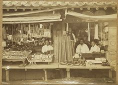 [Korean shopkeepers with wares] ca. 1904. In 1896, the adviser to the Treasury, John McLeavey Brown, ordered the clearing of temporary booths and the widening of main roads to fifty-five feet. Until that time the streets were crowded with temporary booths and the stalls. The stall shown in the picture was one of the booths that had uniform looks and were erected on spare ground beyond the roadway. Source: Pratt, Keith. Old Seoul, 2002. p. 31.