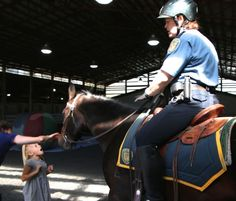 The first arrivals at the Seattle Police Mounted Patrol Unit's second annual Open House found it pretty exciting to meet the horses face to face. Above, Officer Laura Wollberg and Chance impressed a young visitor. You'll find the horses and officers in and around their barn on the west s