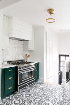 Modern Vintage Kitchen with cabinets in Benjamin Moore's Forest Green. Open shelving. Cement tile. Green cabinets. Green and brass. Tile floor. Patterned tile. Brass hardware. Cabinet hardware.