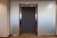 LEVELe Wall Cladding System with Capture panels; insets in ViviChrome Chromis glass with Mirror Mist interlayer and Opalex finish; also shown, Elevator Doors in Bonded Nickel Silver with Dark Patina and Vancouver pattern at Herb Chambers, Boston, Massachusetts