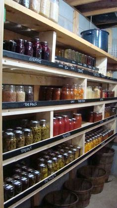 """The 1""""x2""""s that help keep the canning jars from falling are painted with chalkboard paint. Then you can label each section with what is stored in the jars. I like the bushels on the floor underneath too.."""