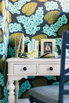 A vibrant blue, white and green guest bedroom includes modern design details and eye-catching wallpaper.