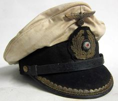 This is a reproduction of a Kriegsmarine U-Boat Captains Peaked cap with 70+ years of ageing and numerous stains and some worn areas. The peak, liner and chinstrap etc. all show good wear and both the inside and outside are heavily stained and aged. Notice the gold emblem and Captains peak ranking are dark and tarnished. www.warhats.com