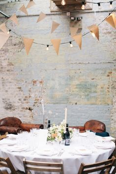 Exposed brick, leather chairs, brown kraft paper bunting & festoon lights industrial urban decor - Image by Lee Robbins Photographic - David Fielden Wedding Dress & Jimmy Choo Shoes for an urban, industrial wedding at MC Motors London City with pastel bridesmaid gowns & Groom in a Vivienne Westwood Suit.