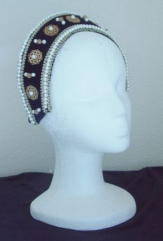 """This crescent headpiece is a replica of the one worn by Catherine of Aragon in Season 1 of The Tudors and reused by Princess Mary in Season 3 It does not have a veil, like a traditional French hood, and was worn with a black snood by Catherine and with a short black lace veil by Mary. It is often times called a """"Crescent""""   $50.00"""