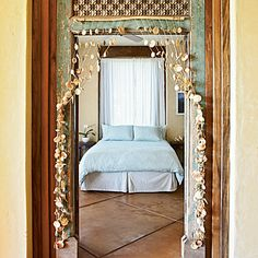 A handcrafted curtain made from locally sourced shells defines the entrance to this Maui bedroom. coastalliving.com