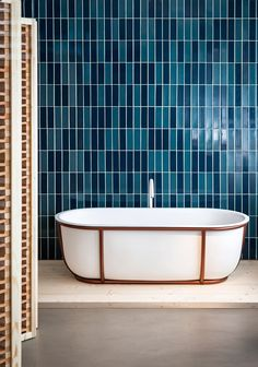 Spanish designer Patricia Urquiola has created a bathtub for Italian brand Agape that is supported by a frame of tubular steel. The curved form of the compact Cuna bath was produced by thermoforming a solid-surface material into the desired shape.