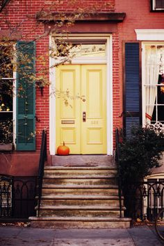 Brick townhouse with yellow painted door - Dark shutters - City sidewalk - Pumpkin on front porch - Fall