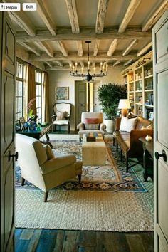 love love love this room- everything from natural beams, door details, double rugs, windows, drapery, bookcase, iron chandelier