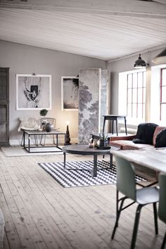 The black and white photos at the end of this long living and dining room go with the Scandinavian feel of the whole room, especially the wood floors.