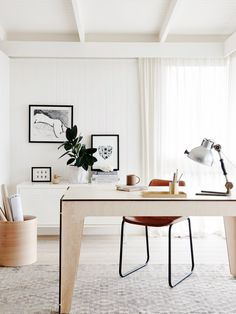 White office space, light wooden table and tabletop accessories, brown leather chair, silver lamp, and black and white wall art