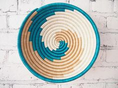 This sisal, woven basket is approximately 12 in diameter and handmade by our artisans in Gitarama, Rwanda. The women grow their own sisal plants, extract the fibers, then hand-dye and weave them into these beautiful works of art. The sisal is woven around sweetgrass, a fragrant grass with